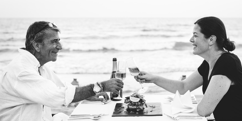 Una coppia brinda felice sulla spiaggia, il piacere di ascoltare ti fà stare bene in compagnia